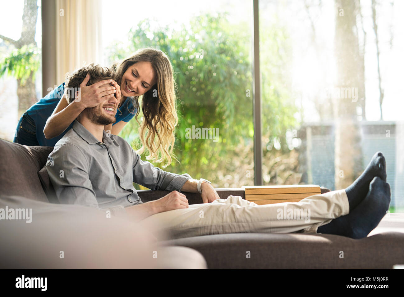 Smiling woman covering her boyfriend's eyes on sofa at home - Stock Image