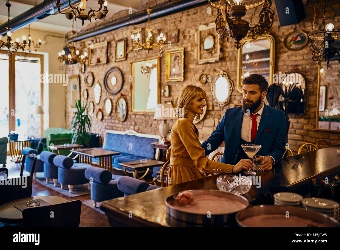 Elegant couple having a drink in a bar - Stock Image