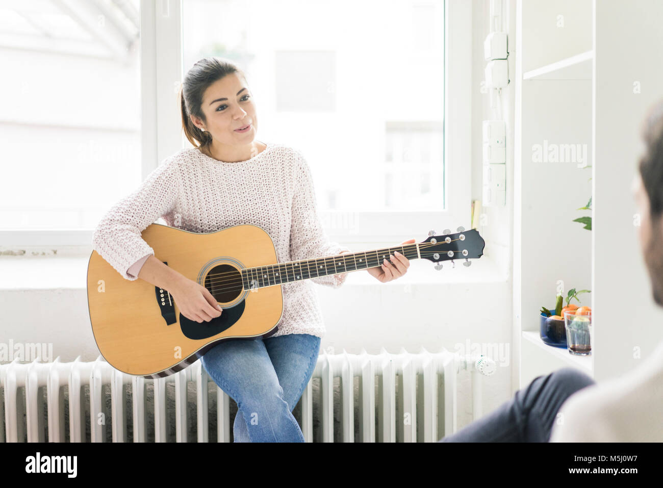 Woman playing guitar for man - Stock Image