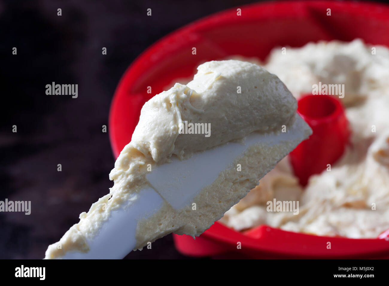 Dough scraper with fresh batter, close-up Stock Photo