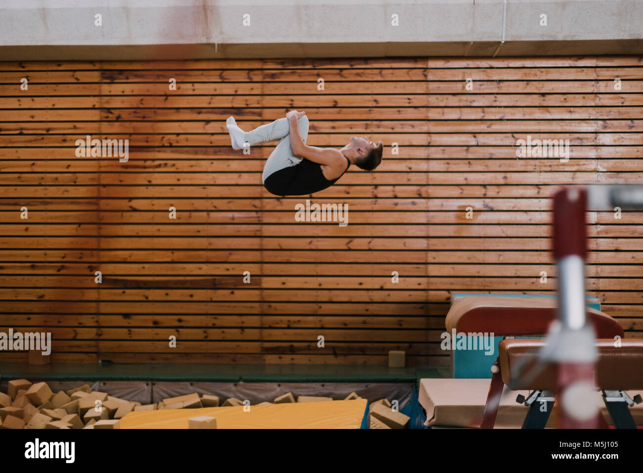 Gymnast exercising at vaulting table in gym - Stock Image