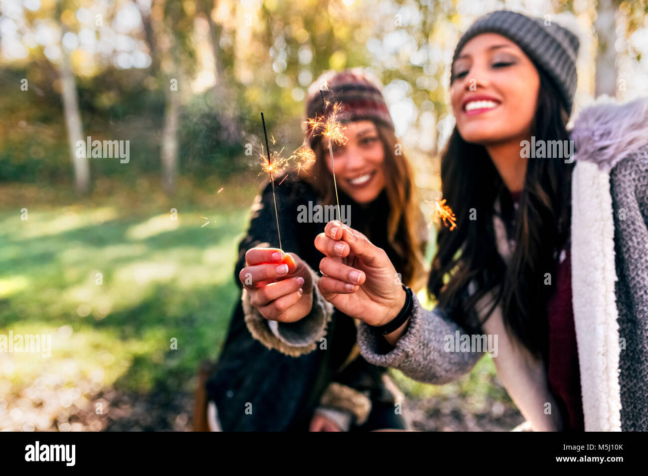 Two gorgeous women having fun with sparklers in an autumnal forest - Stock Image