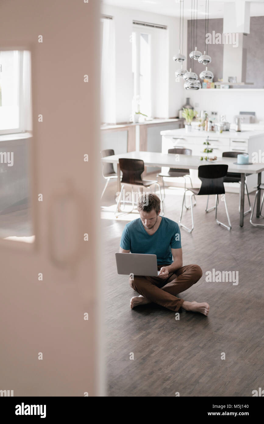 Man sitting on the floor in the kitchen working on laptop - Stock Image