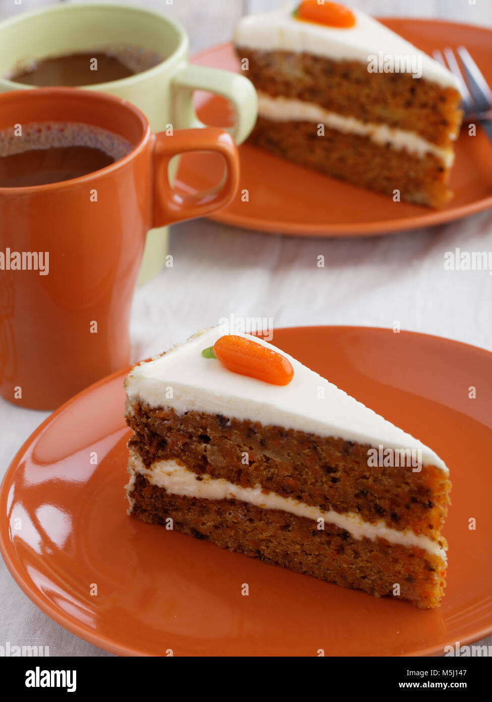 Two slices of carrot cake with hot chocolate - Stock Image