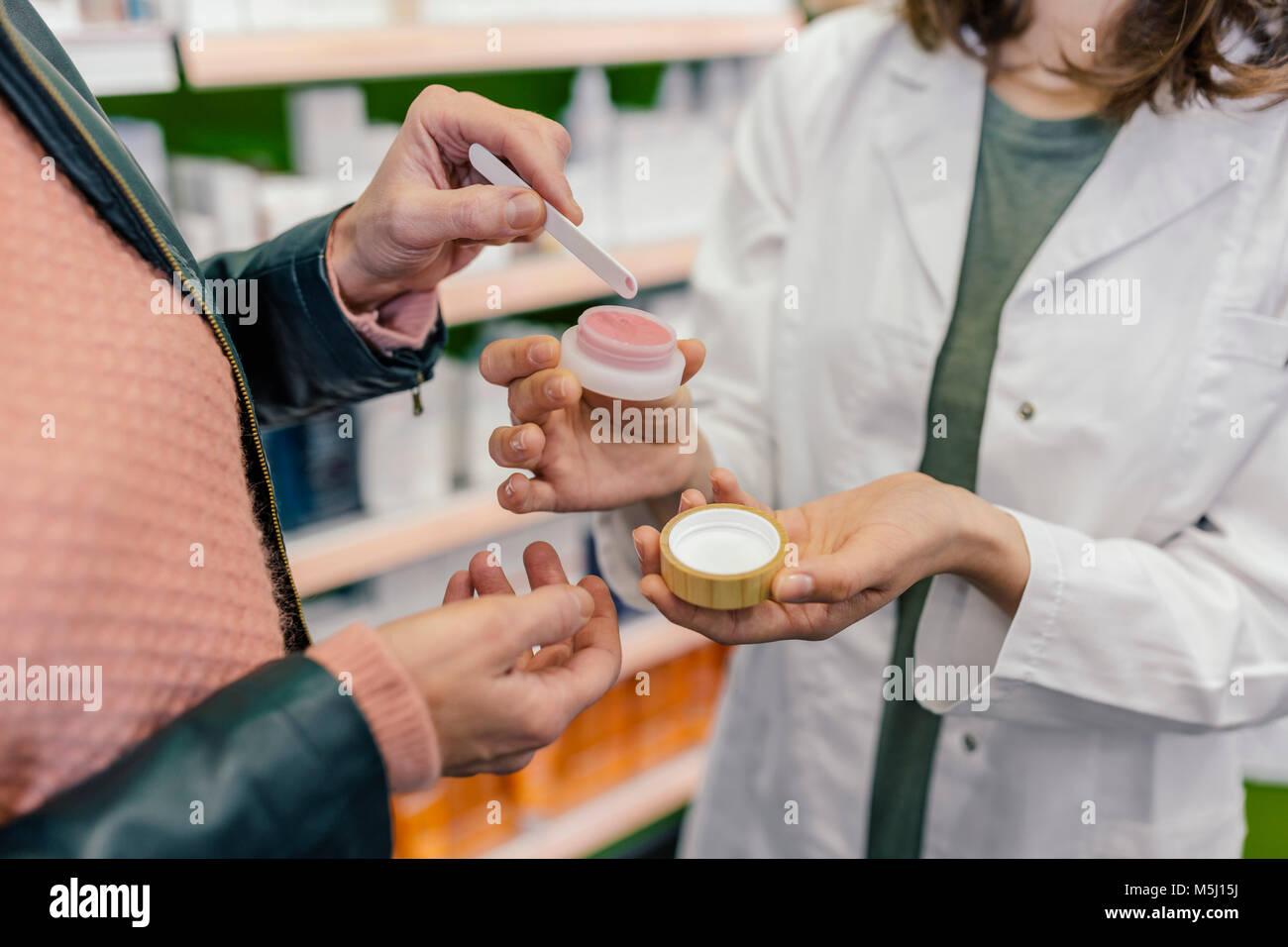 Customer testing cosmetics in pharmacy - Stock Image