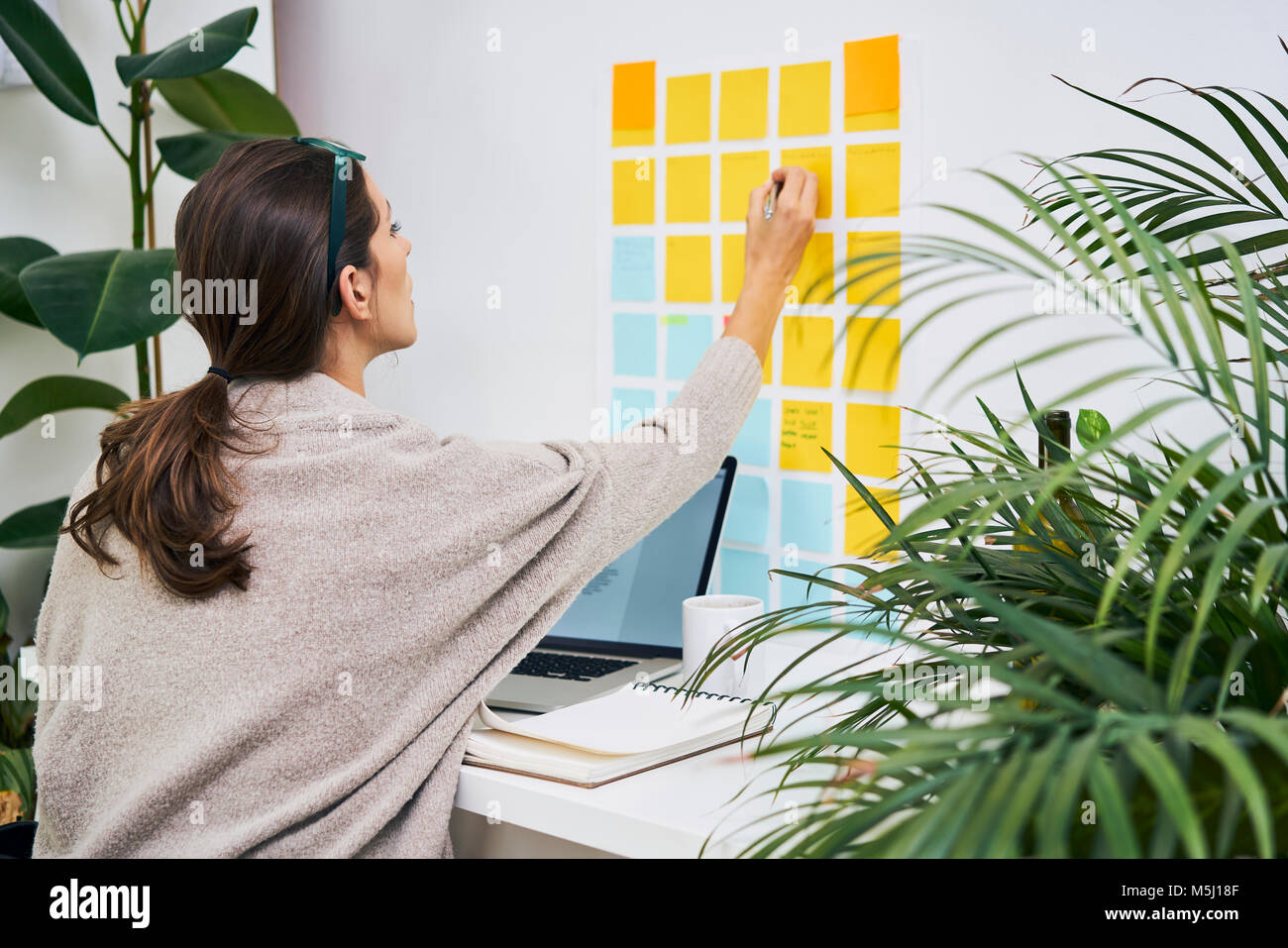 Young woman with laptop on desk working with adhesive notes on the wall - Stock Image