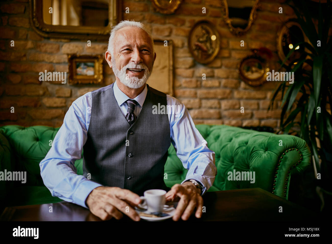 Portrait of elegant senior man sitting on couch in a cafe smiling Stock Photo