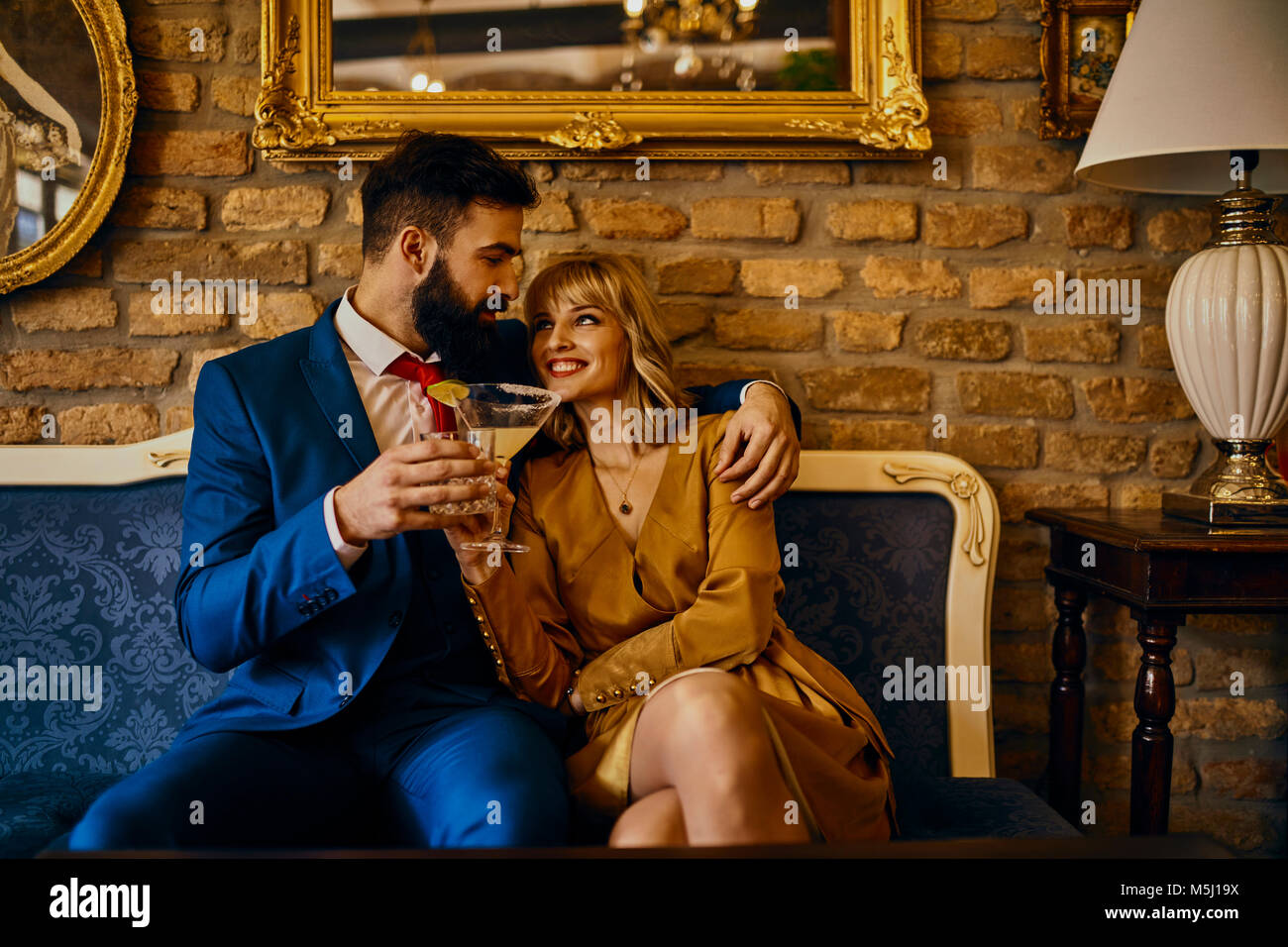 Happy elegant couple with drinks sitting on couch embracing - Stock Image