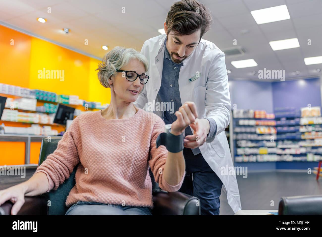Pharmacist taking blood pressure of customer in pharmacy - Stock Image
