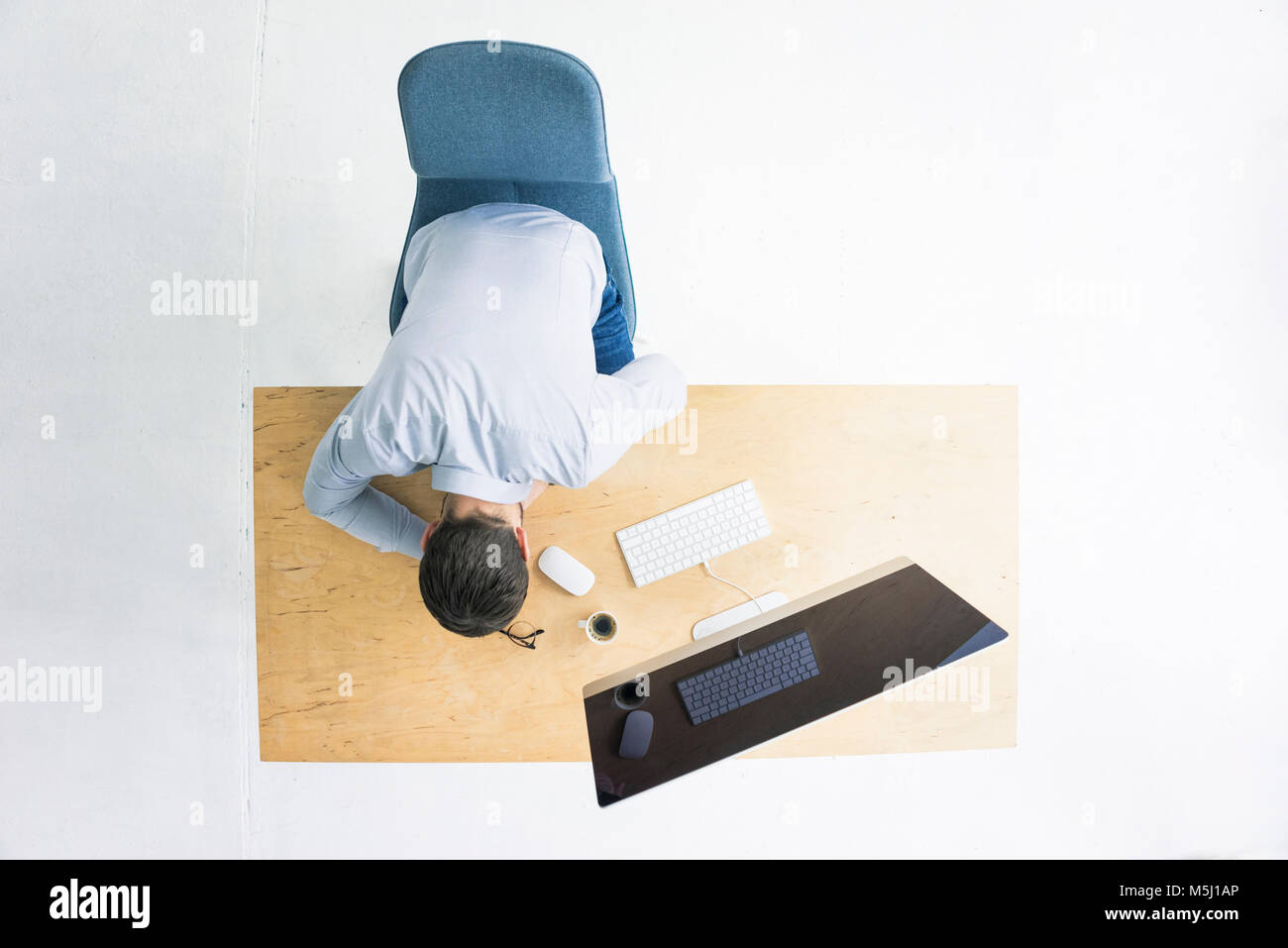Businessman sitting at desk in office seen from above Stock Photo