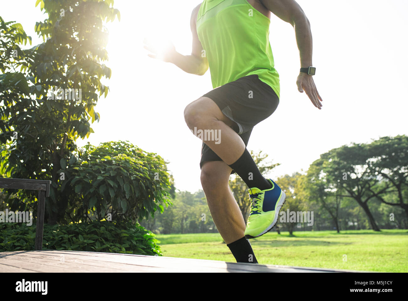 Runner training running up stairs, close up - Stock Image