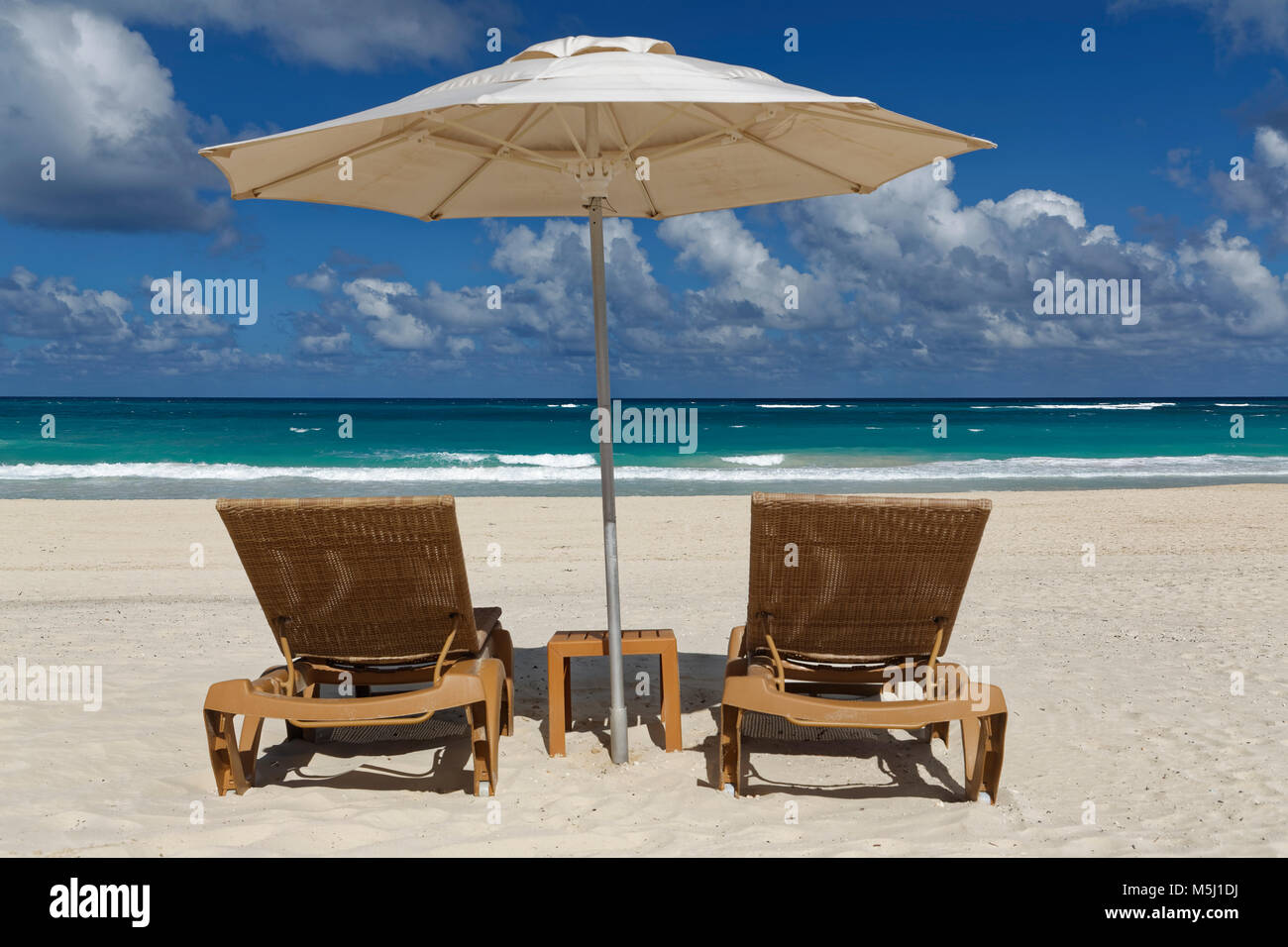 Carribean, Dominican Republic,  Playa Bavaro, beach with two sun loungers and beach umbrella - Stock Image
