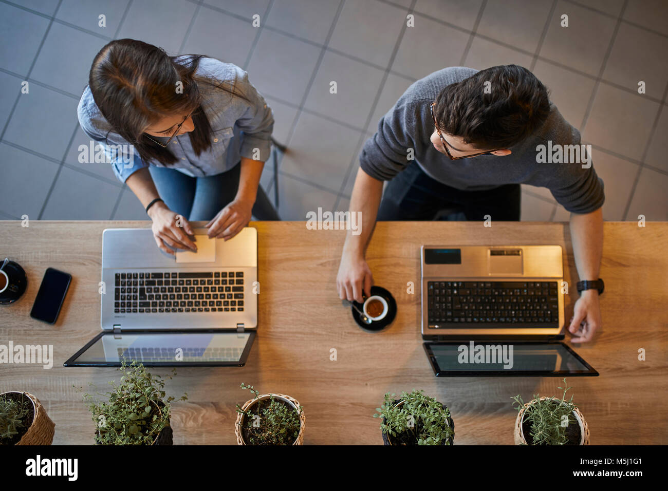 Top view of young woman and man in a cafe with laptops discussing - Stock Image
