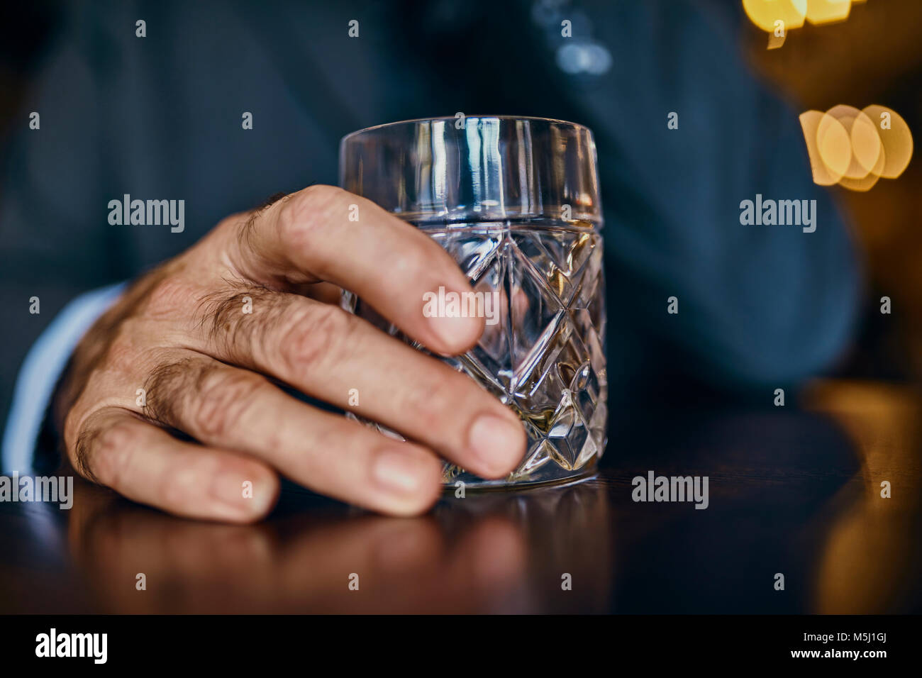 Close-up of man in a bar with tumbler - Stock Image