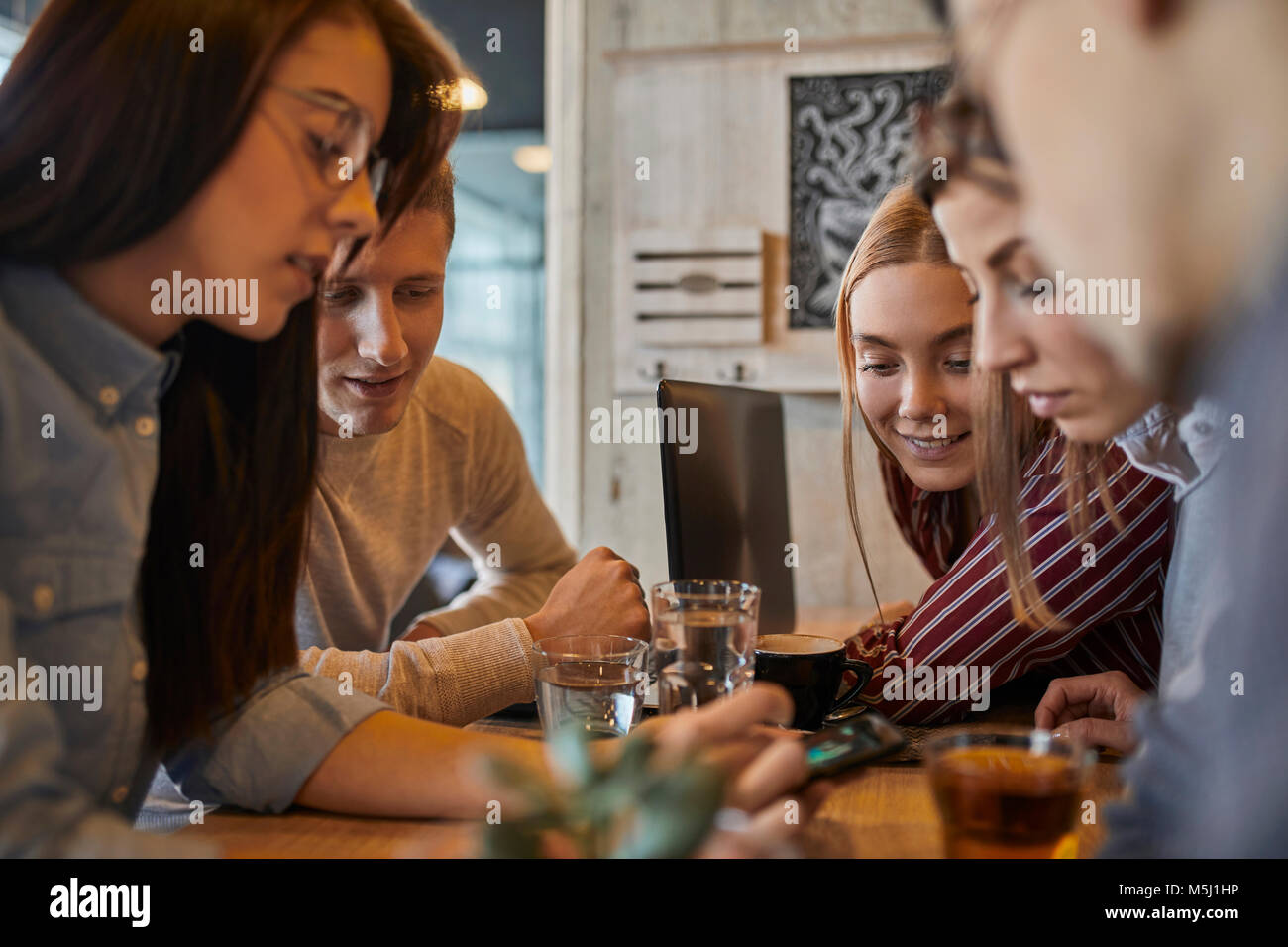 Group of friends sitting together in a cafe sharing smartphone - Stock Image
