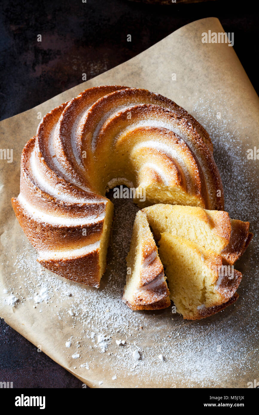 Sliced Gugelhupf sprinkled with icing sugar on parchment paper - Stock Image