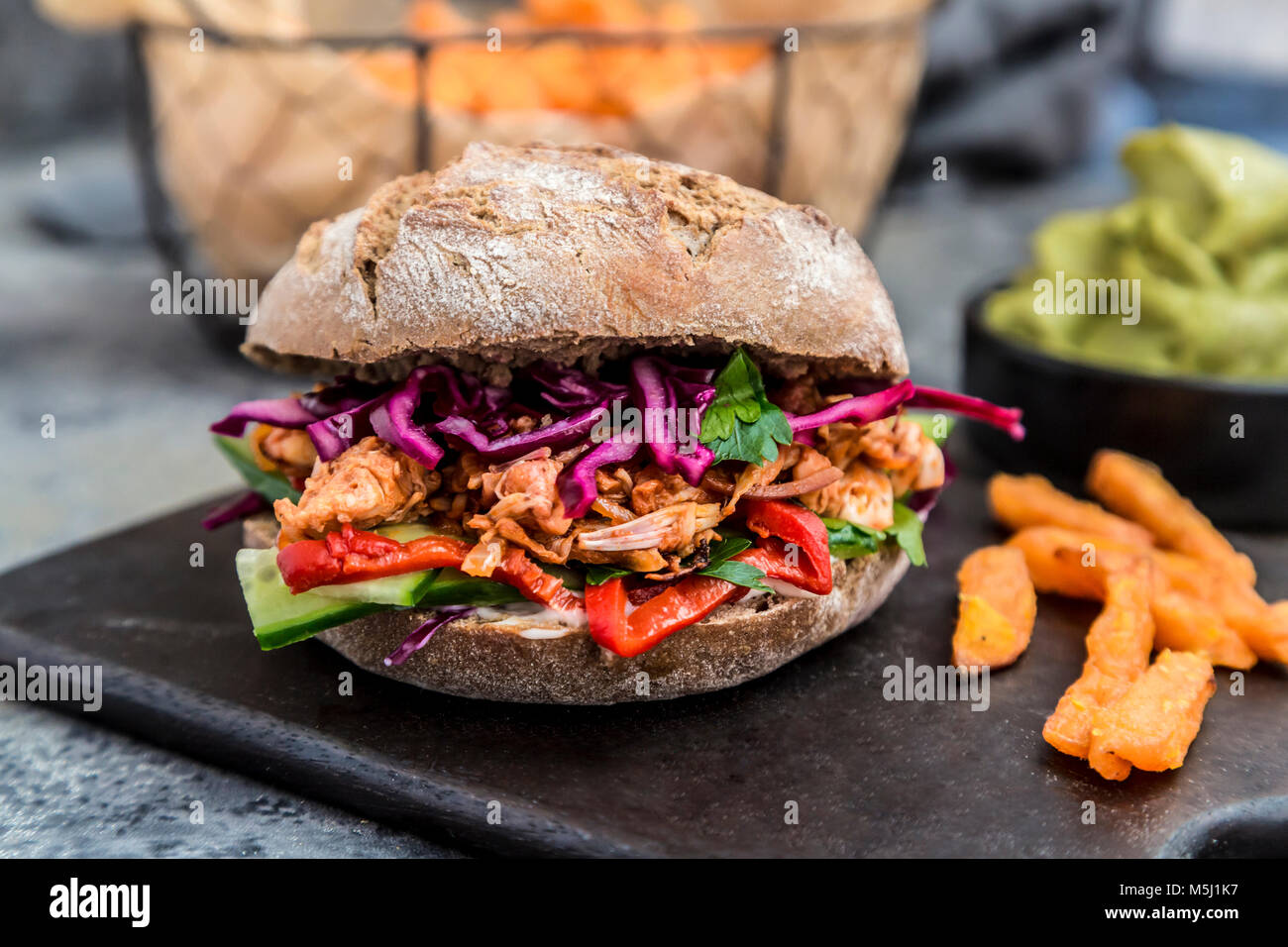 Pulled pork jackfruit burger, jackfruit, red cabbage, cucumber, paprika, parsley - Stock Image