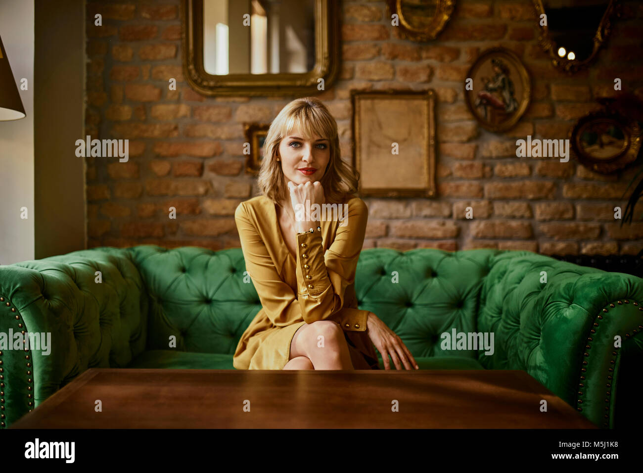 Portrait of elegant woman sitting on a couch - Stock Image
