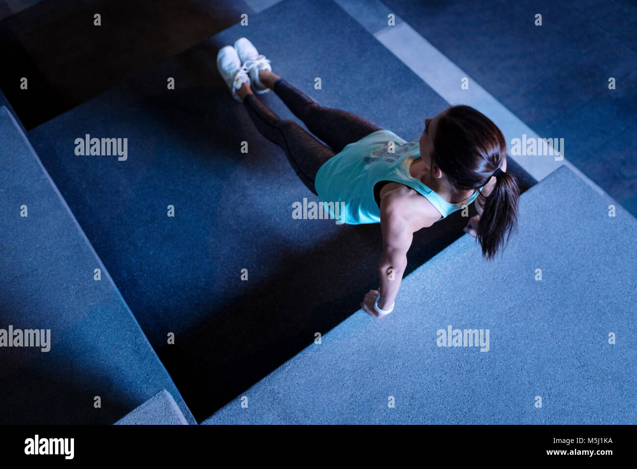 Young woman doing reverse pushups in modern urban setting at night - Stock Image