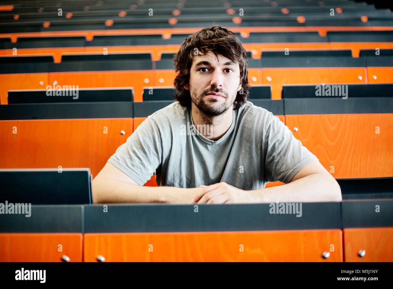 Portrait of student in auditorium at university - Stock Image