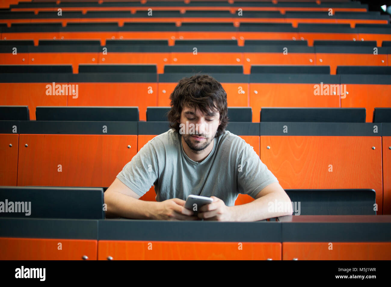Portrait of student in auditorium at university looking at cell phone - Stock Image