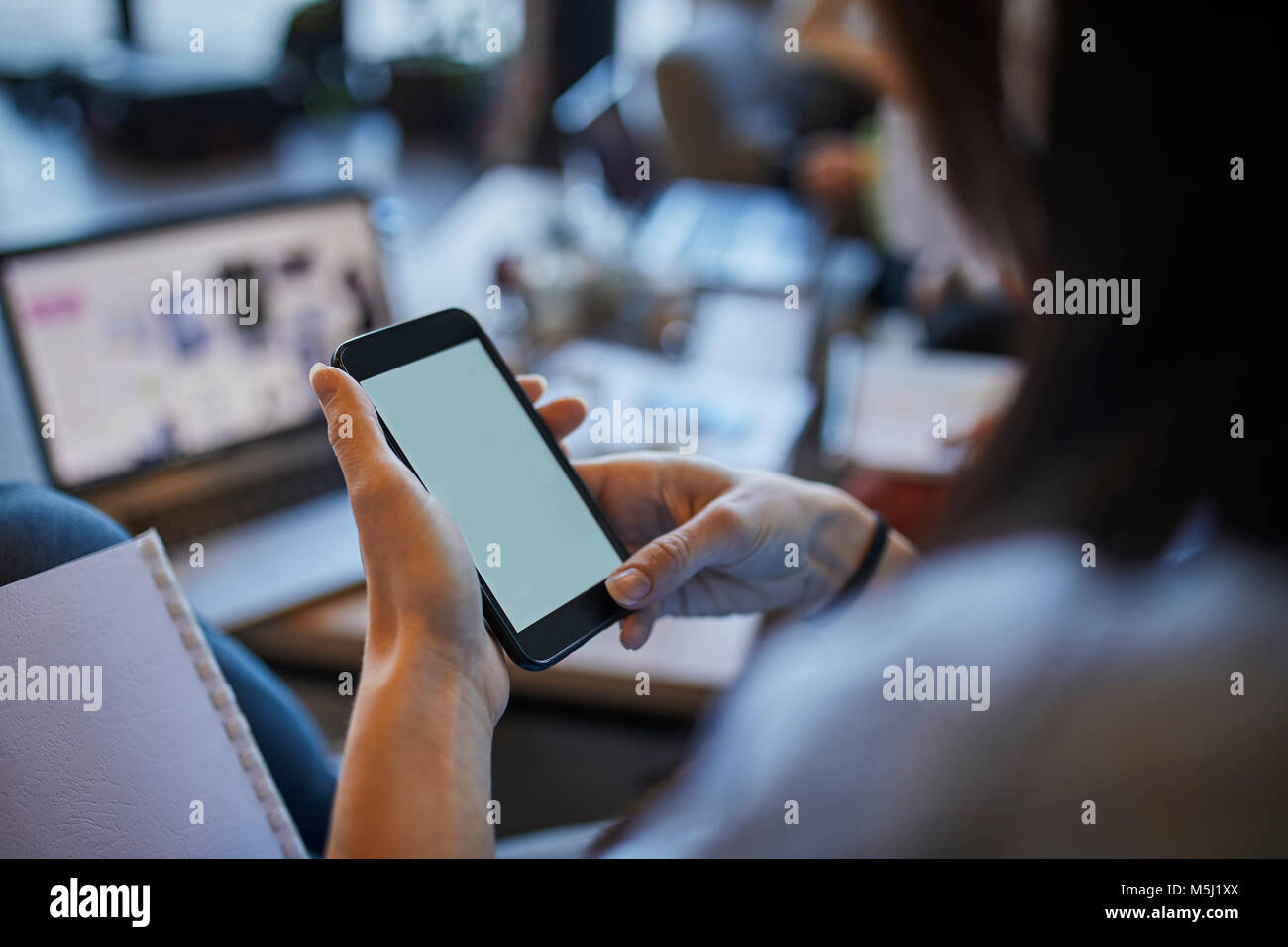 Young woman in cafe using smartphone with laptop in background - Stock Image