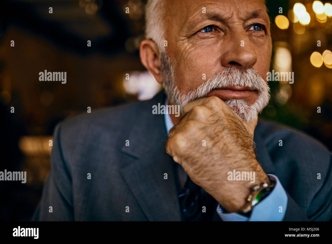 Portrait of elegant senior man thinking - Stock Image