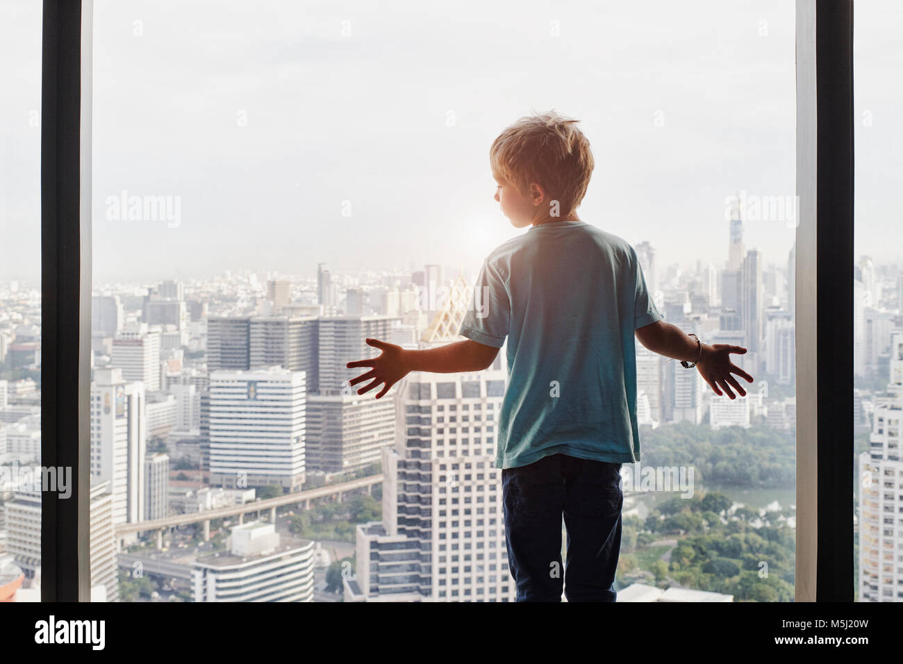 Thailand, Bangkok, boy looking through window at cityscape - Stock Image