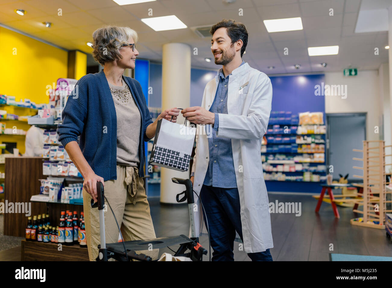 Pharmacist giving bag of medicine to customer with wheeled walker in pharmacy - Stock Image