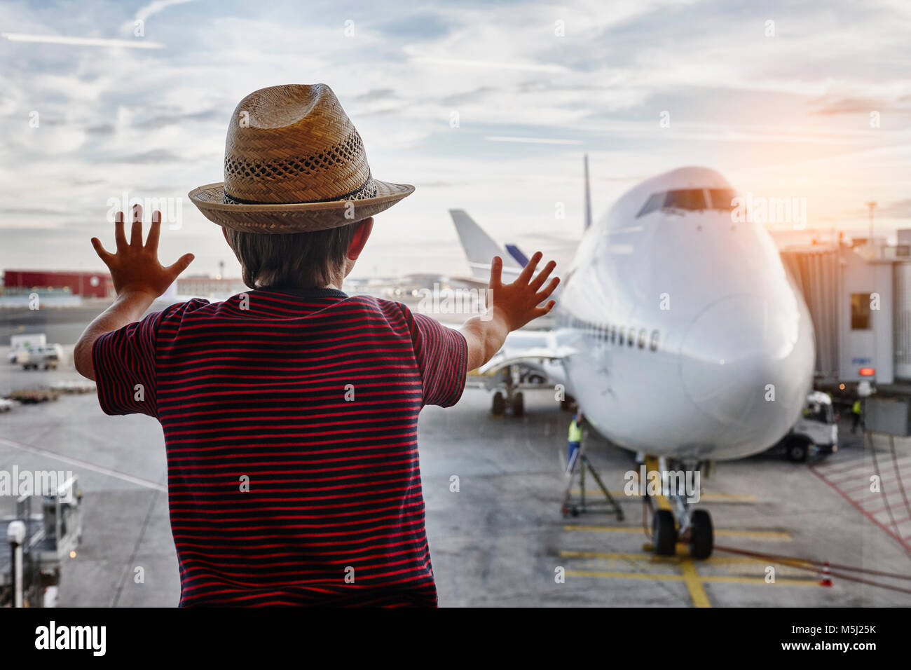 Boy wearing straw hat looking through window to airplane on the apron - Stock Image