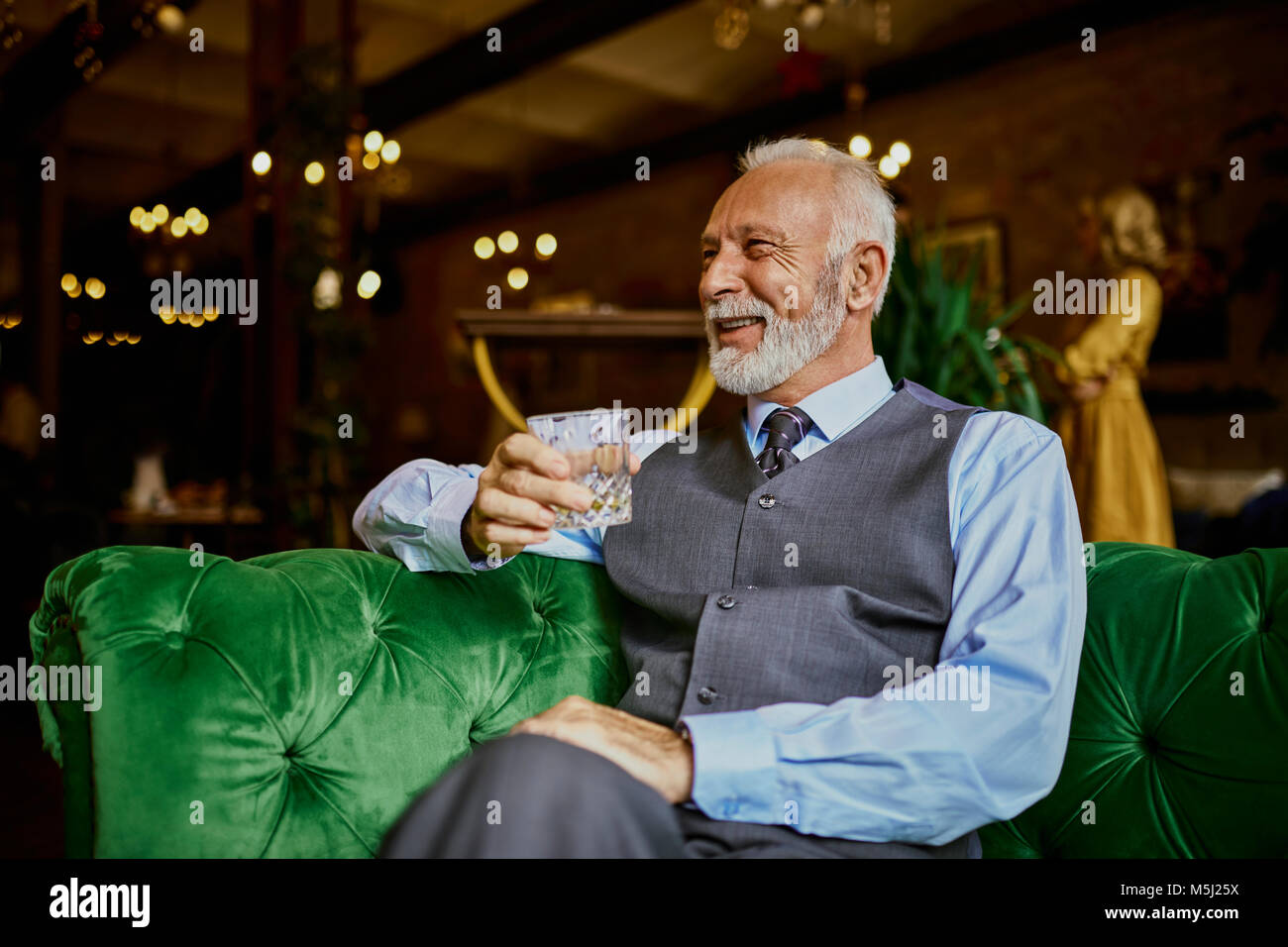 Portrait of elegant senior man sitting on couch in a bar holding tumbler - Stock Image