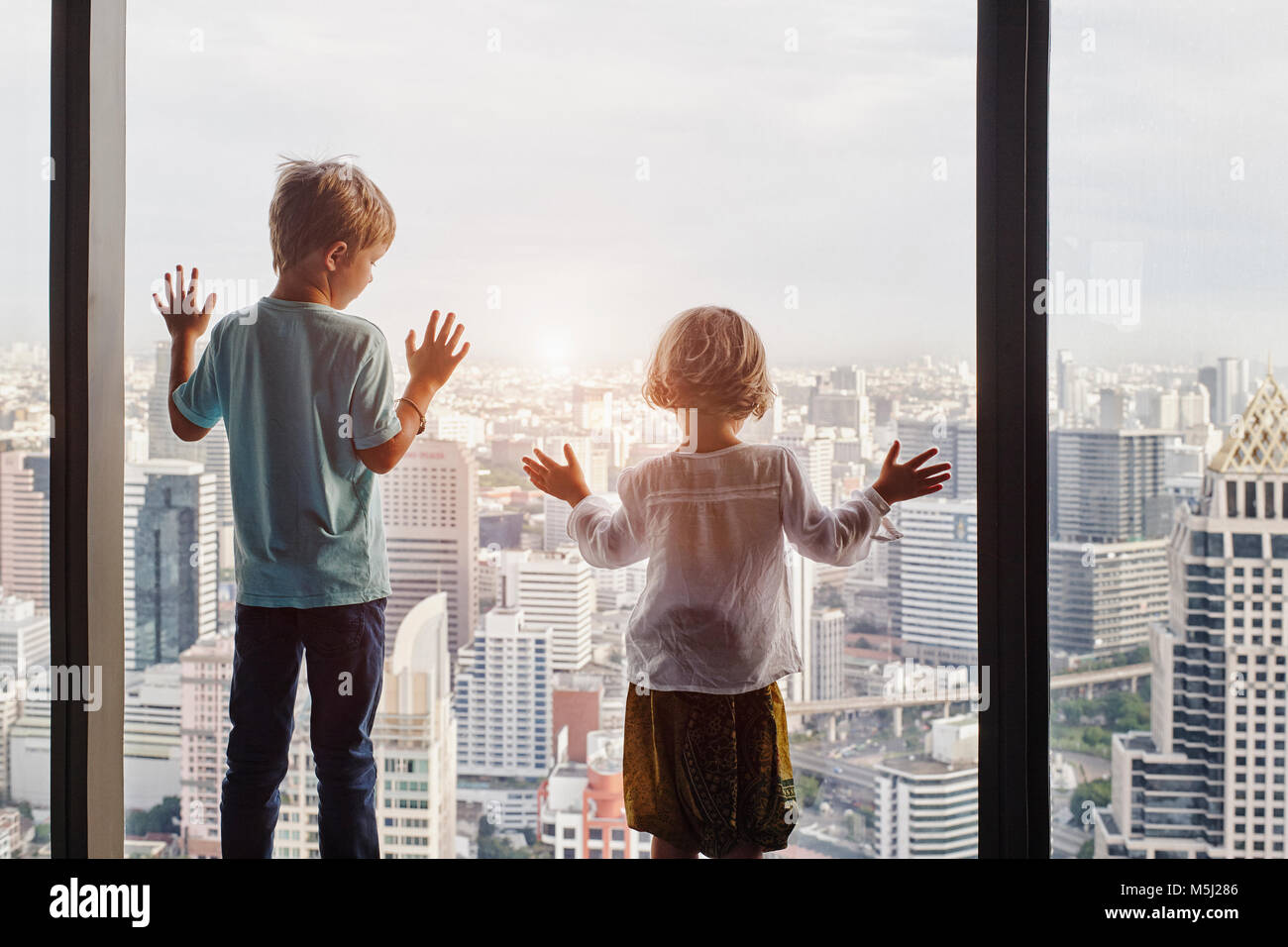 Thailand, Bangkok, boy and little girl looking through window at cityscape - Stock Image