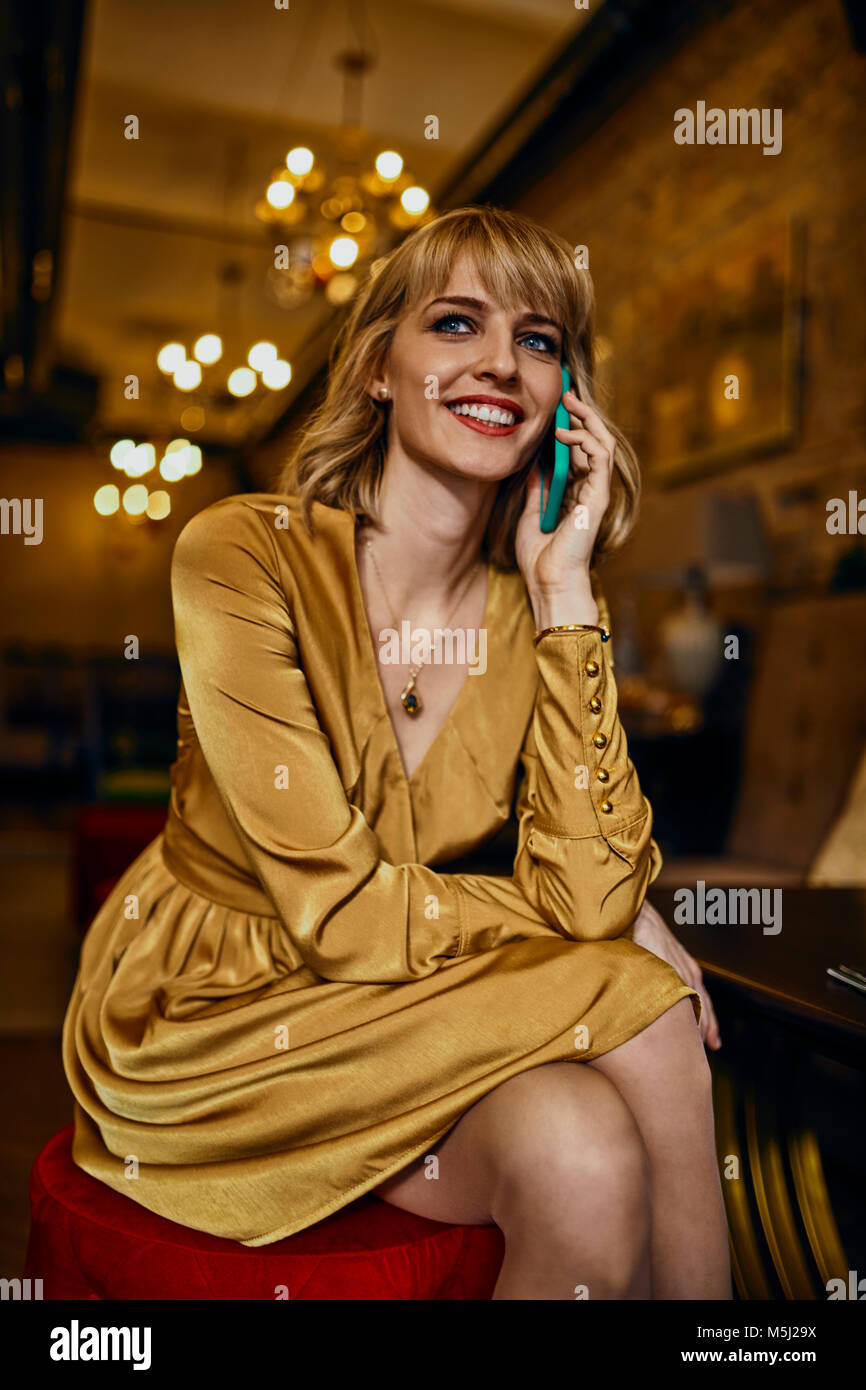 Portrait of smiling elegant woman in a bar on cell phone - Stock Image