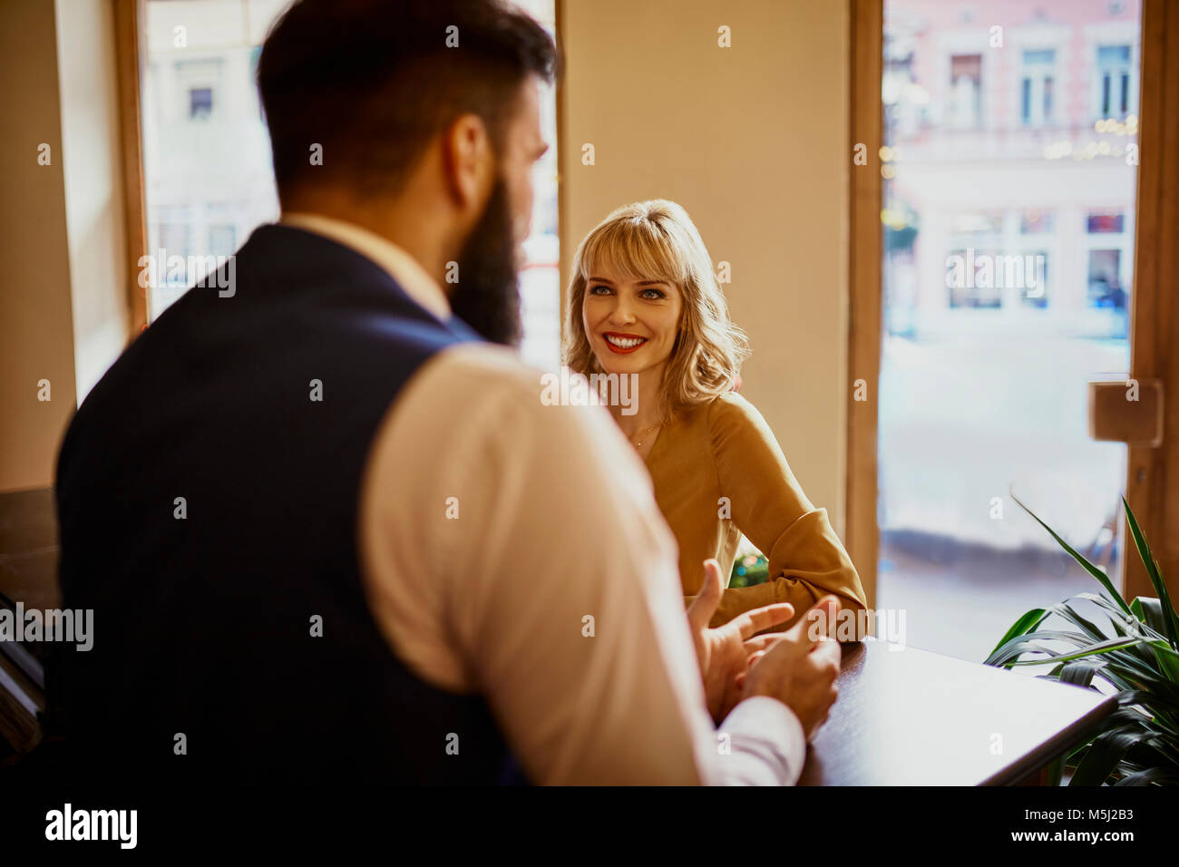Elegant woman smiling at man in a bar - Stock Image