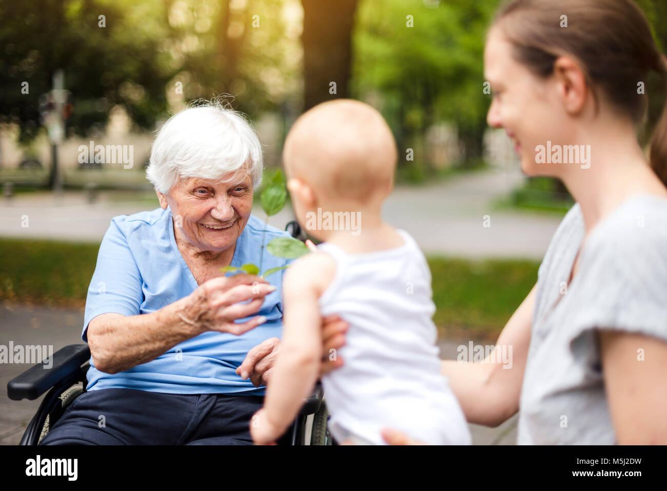 Portrait of happy senior woman with daughter and granddaughter in a park - Stock Image