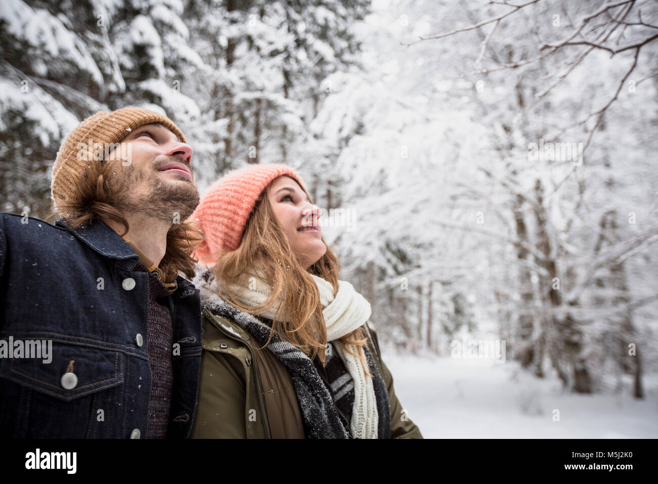 Smiling couple in winter forest watching snow fall Stock Photo