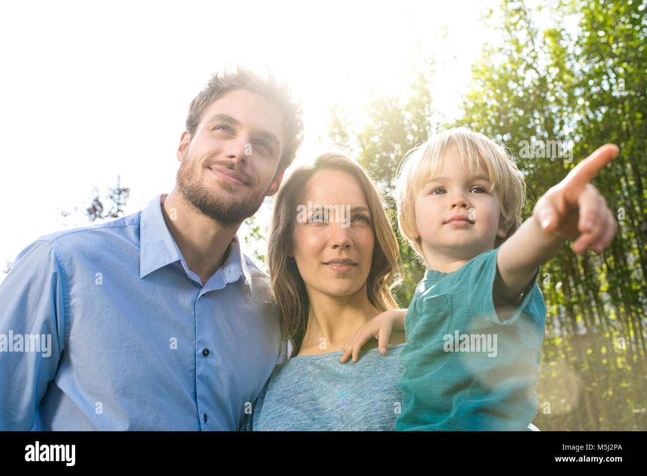 Smiling family in front of bamboo plants with son pointing his finger - Stock Image