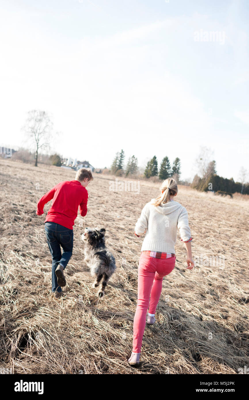 Man and woman with dog running on field - Stock Image