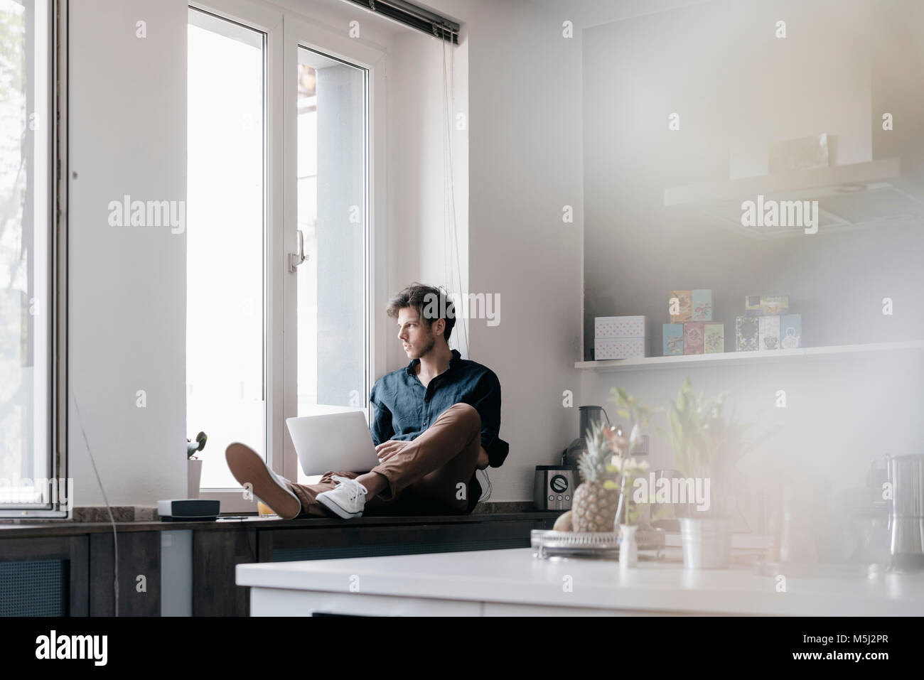 Young man with laptop sitting on window sill in a loft looking out of the window - Stock Image