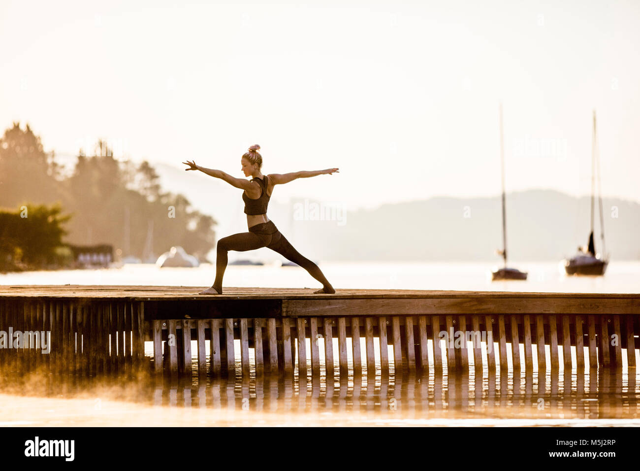 Woman practicing yoga on jetty at a lake - Stock Image