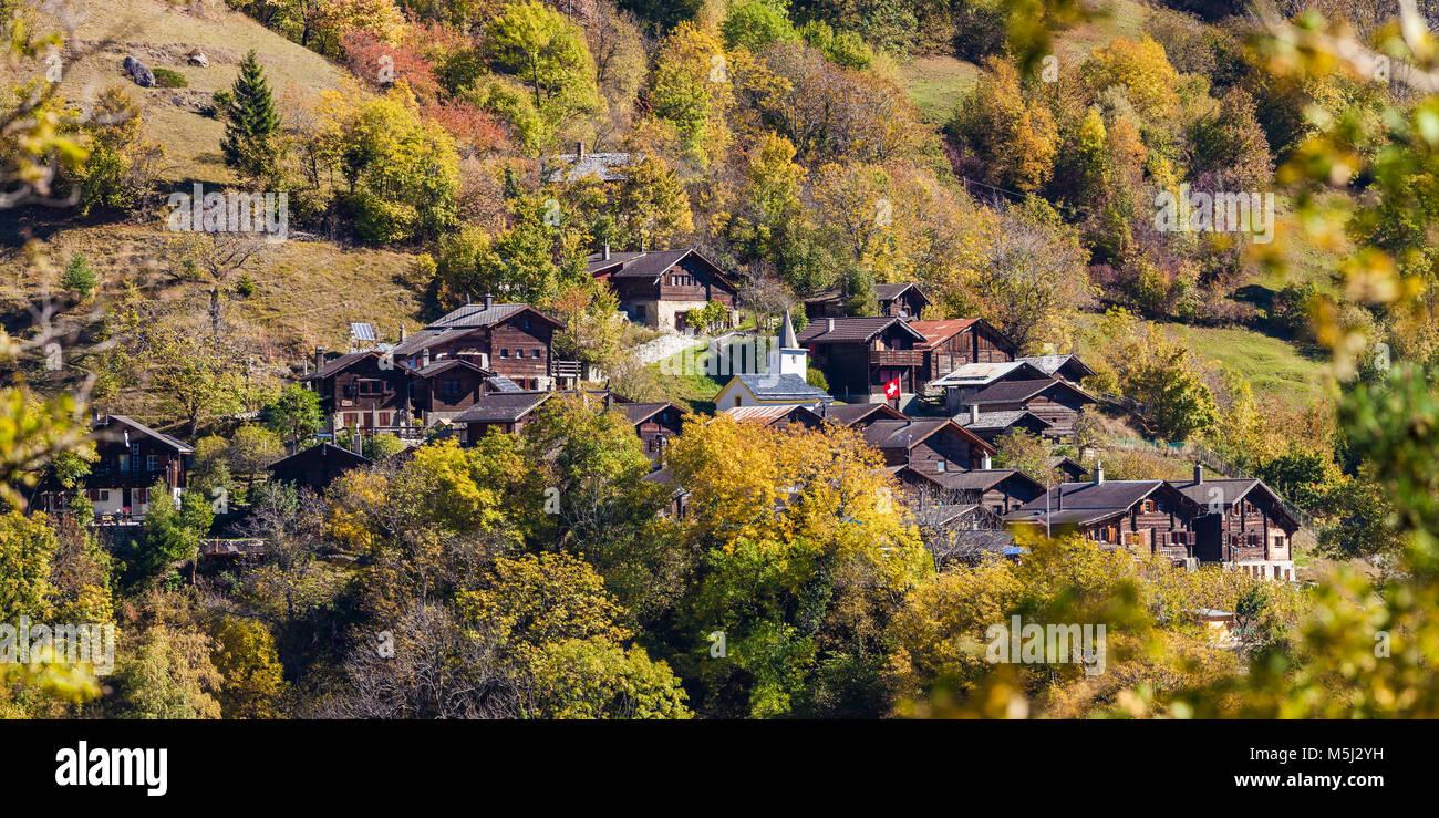 Schweiz, Kanton Wallis, Tschingeren, Bergdorf bei Albinen,  Chalets, Schweizer Fahne, Herbst, Herbstbäume - Stock Image