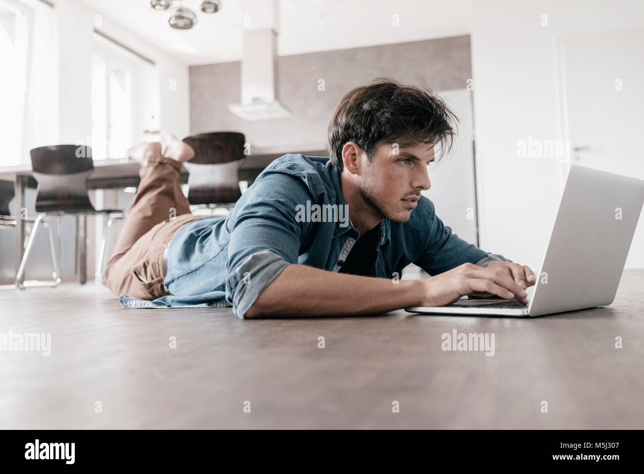 Man lying on the floor in a loft using laptop - Stock Image