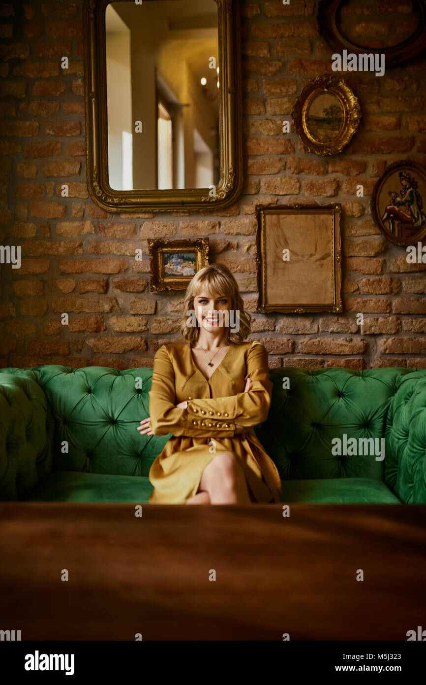 Portrait of smiling elegant woman sitting on a couch - Stock Image