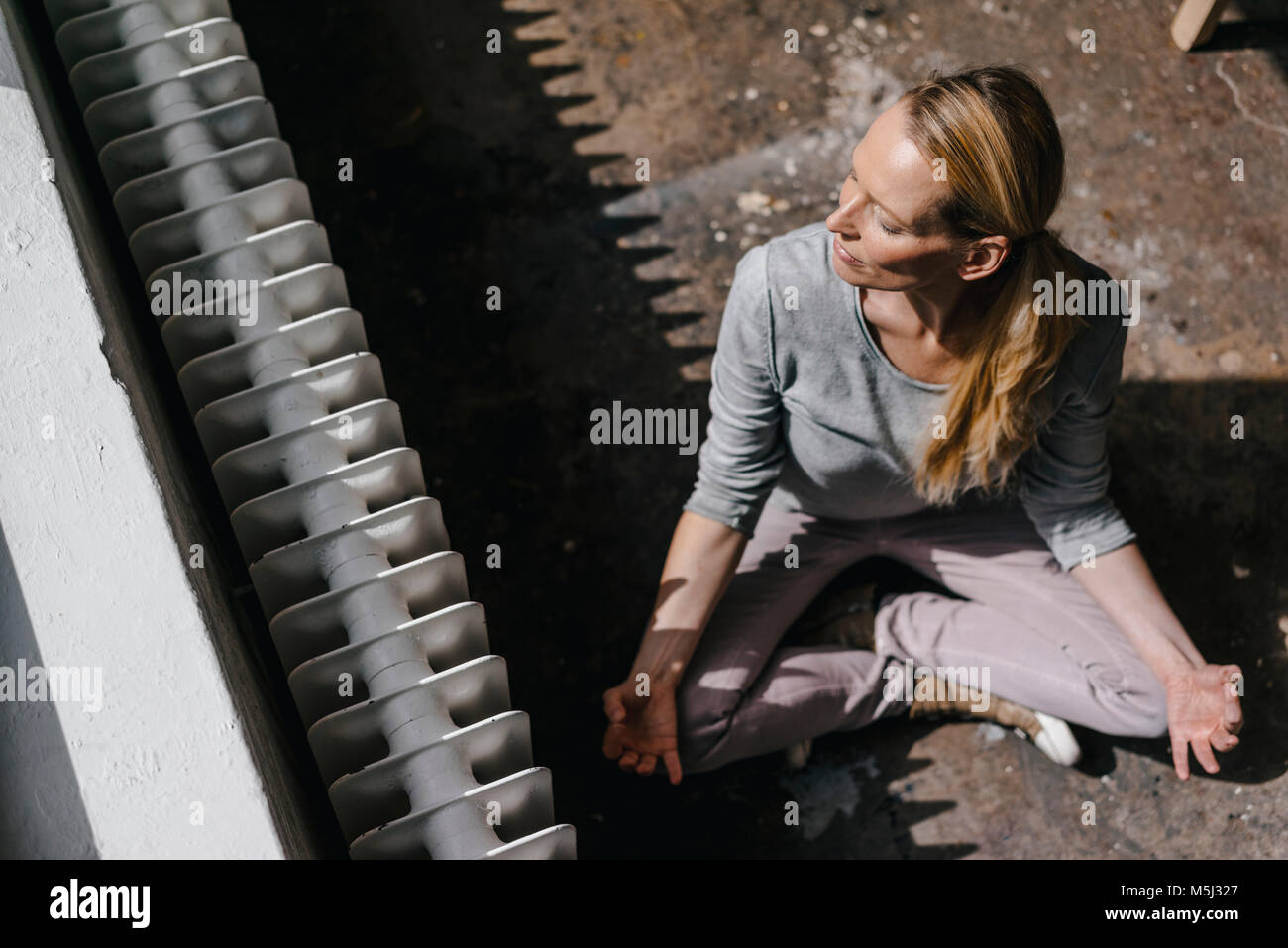 Woman sitting on the floor practicing yoga - Stock Image