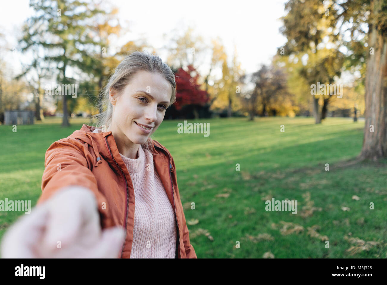 Portrait of young woman reaching out hand in autumnal park - Stock Image