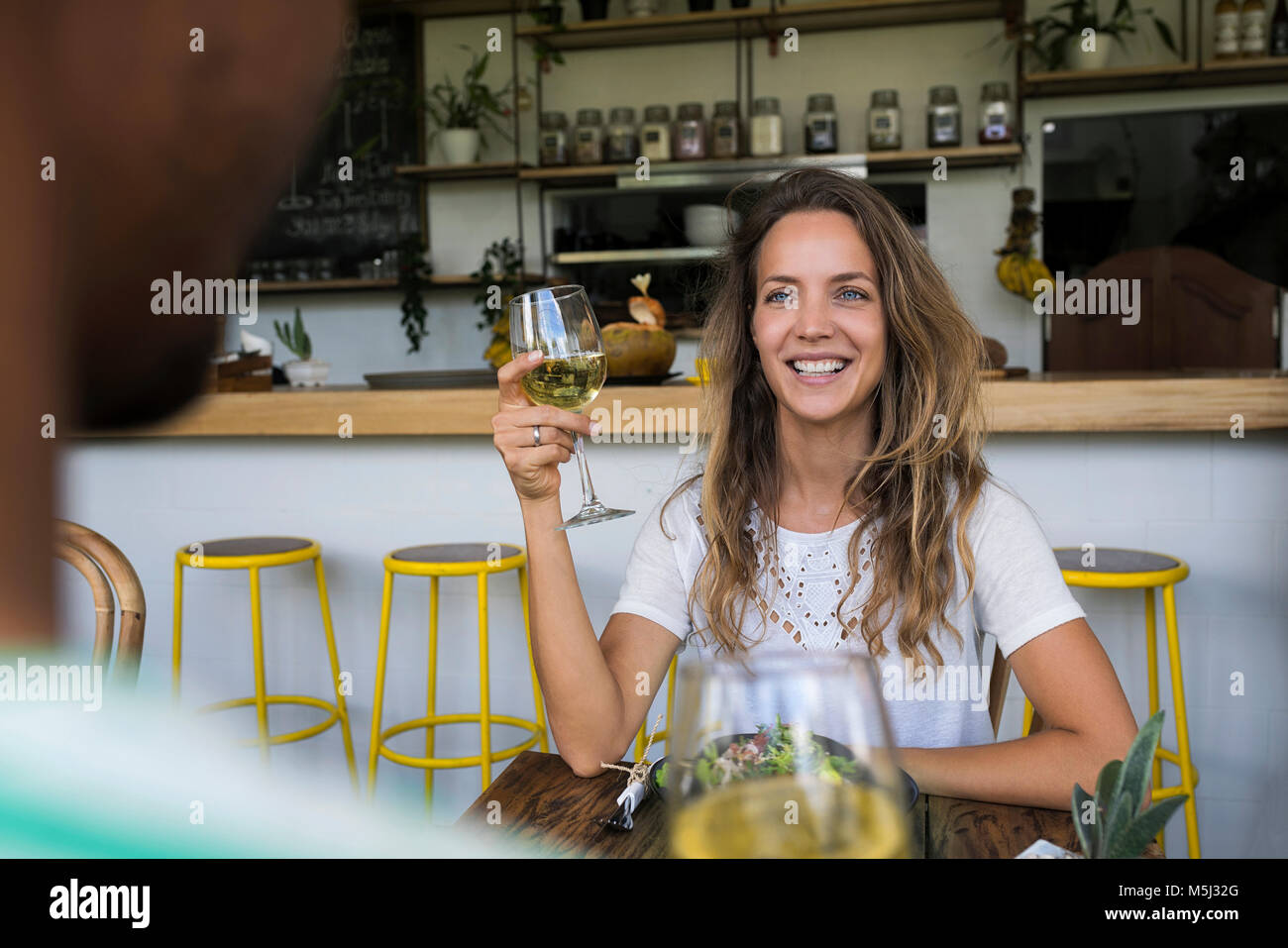 Smiling woman with glass of wine looking at man in a cafe - Stock Image