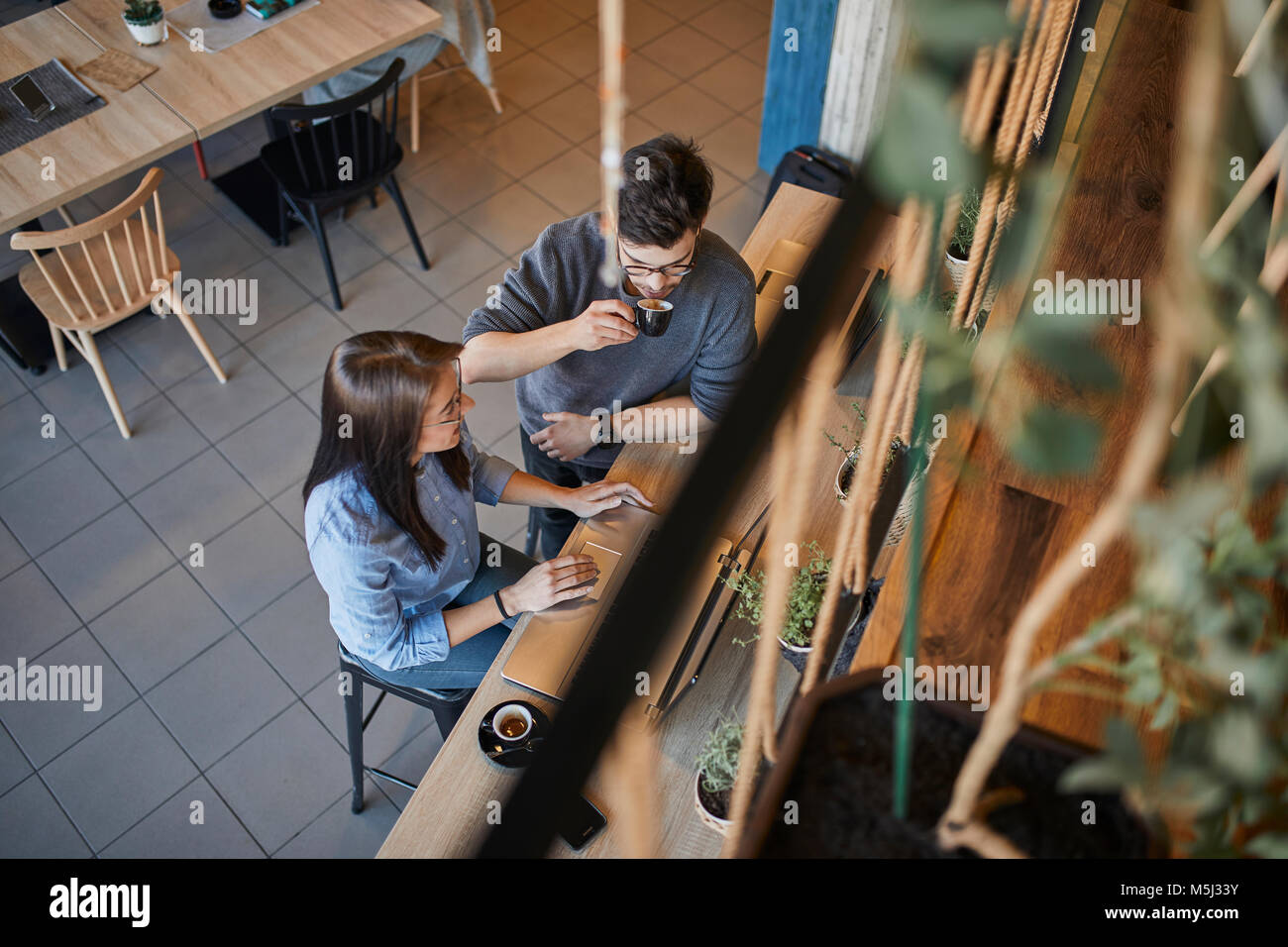 Young woman and man in a cafe with laptops talking and drinking espresso - Stock Image