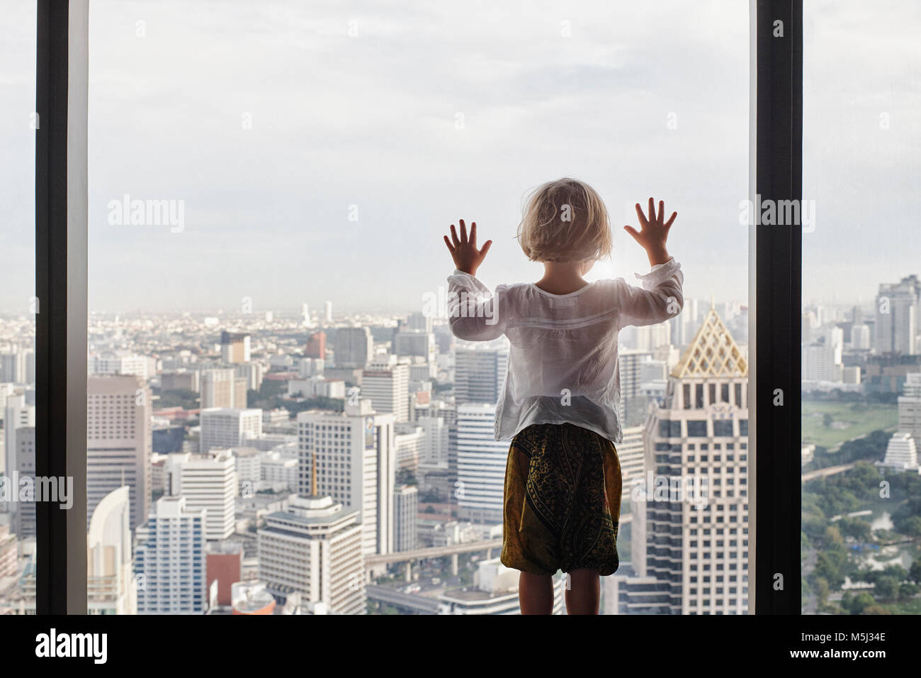 Thailand, Bangkok, little girl looking through window at cityscape - Stock Image