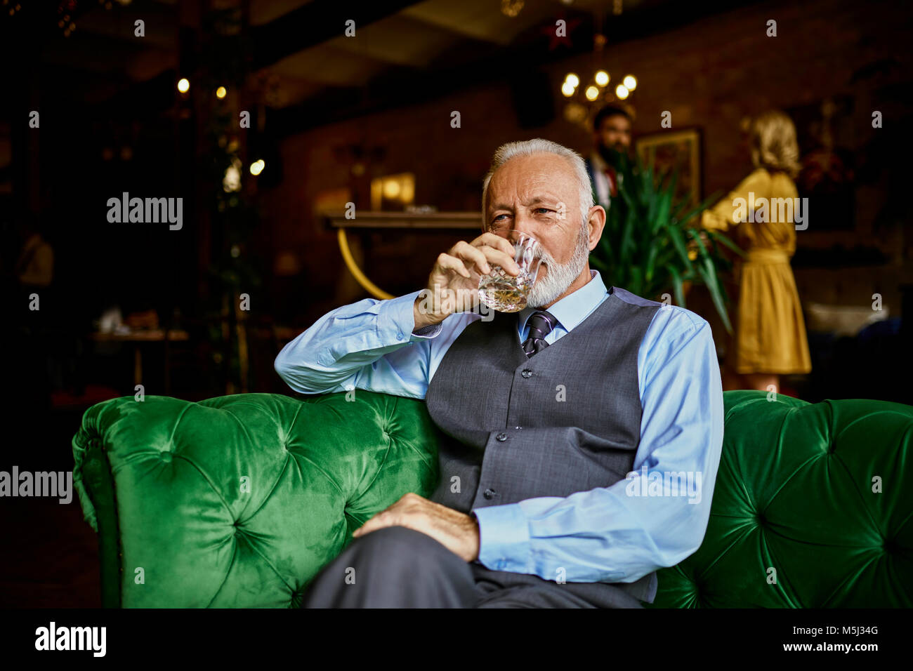 Portrait of elegant senior man sitting on couch in a bar drinking from tumbler - Stock Image