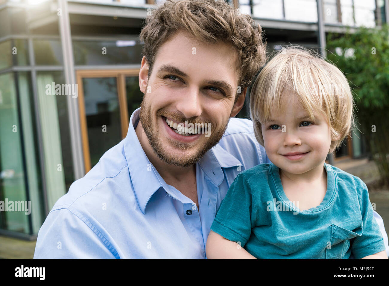 Portrait of smiling father with son in front of their home - Stock Image